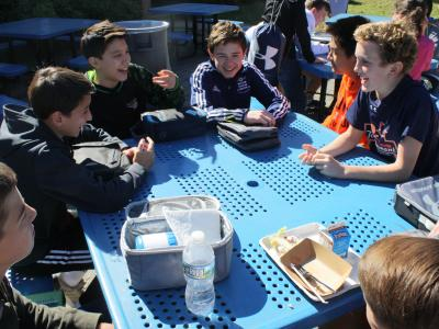 Students enjoying the nice fall weather in the outdoor cafeteria.
